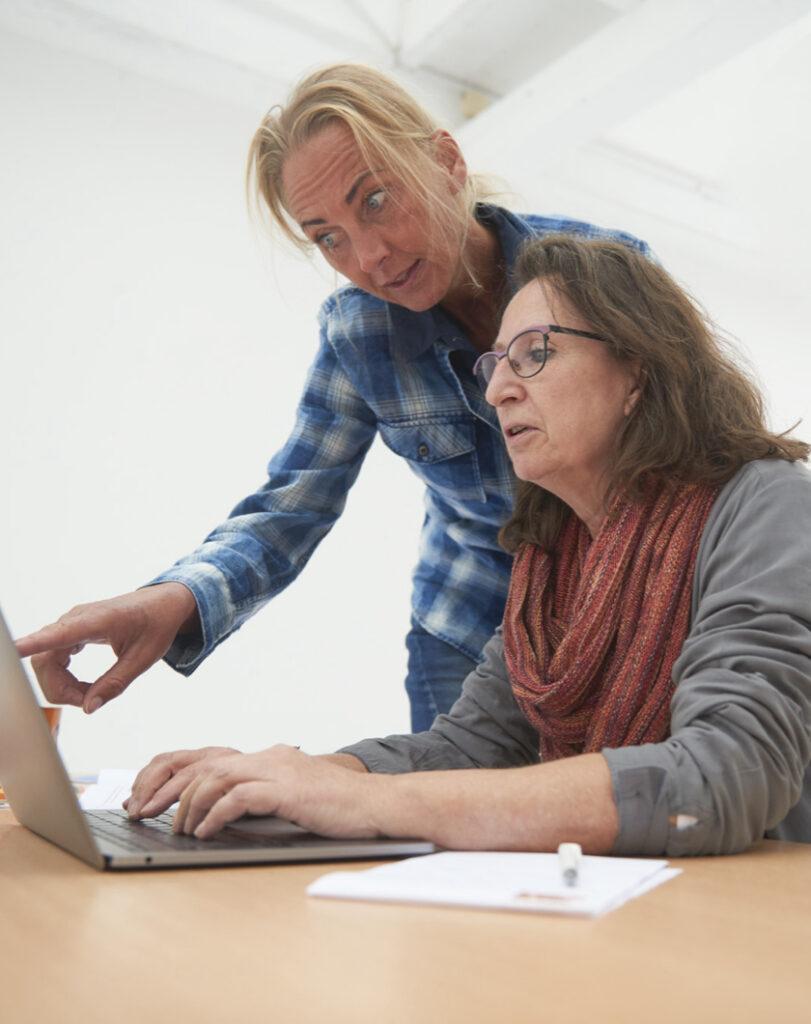 Twee vrouwen achter een laptop.
