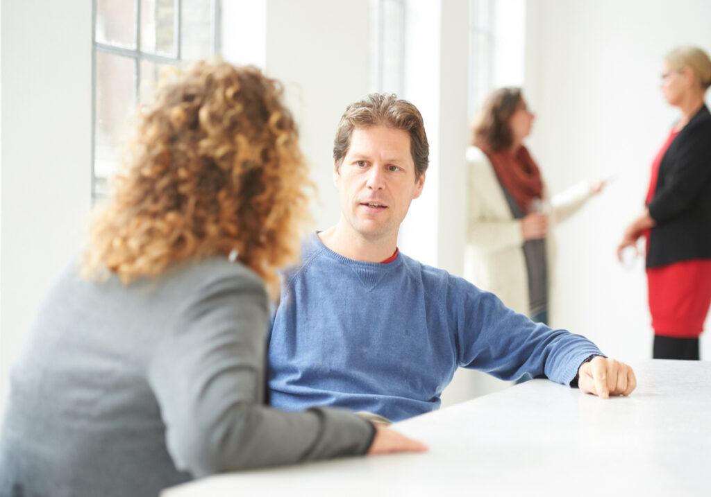Twee mensen in een bespreking.